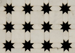 White marble wall with star shape cut-outs. Close-up of Jaigurudeo Temple wall, India
