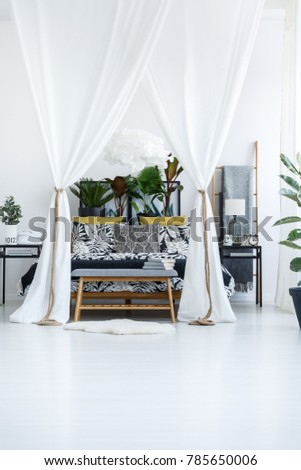 White marquees above bed with plants on the bedhead in bright bedroom interior with wooden bench and rug #785650006