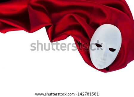 White mask on red silk fabric, theatre concept