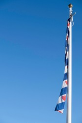 White mast with the flag of the province of Friesland. Blue with seven red seeblatts (or 'Pompebled') and four blue and three white diagonal stripes. Frisian flag at blue sky