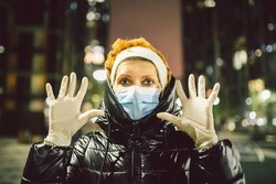 White medical gloves dress on hands adult woman on street city europe during the lockdown quarantine covid19, protective mask face, cityview evening.Personal health protection coronavirus infection.