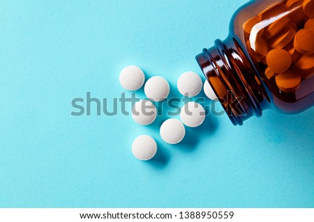 White medical pills and tablets spilling out of a drug bottle. Macro top down view with copy space.
