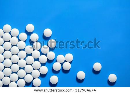 White medical pills on blue background.