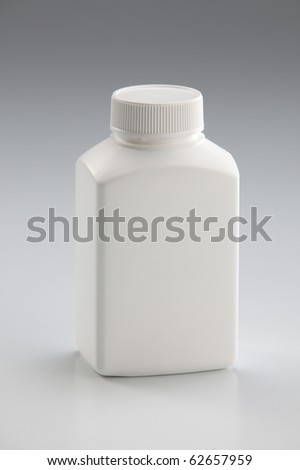 White medicine bottle closed on plain background