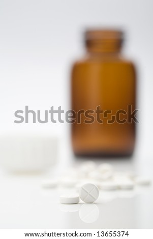 White medicine pills with medicine bottle - stock photo