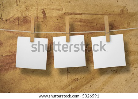 White memos on a clothesline. Rough and grungy looking paper background.