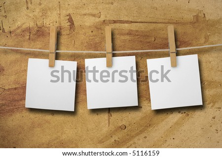 White memos on a clothesline. Rough and grungy looking paper background. New version with closer shadow.