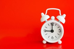 White metal alarm clock on a red background. Nine o'clock. Copy space