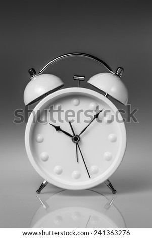 White metal alarm clock with two bells on grey gradient background