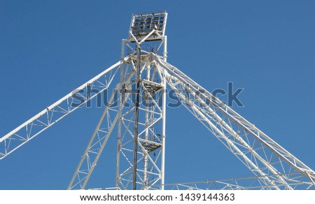 White metal floodlight towers with bright blue sky and space for text or copy #1439144363