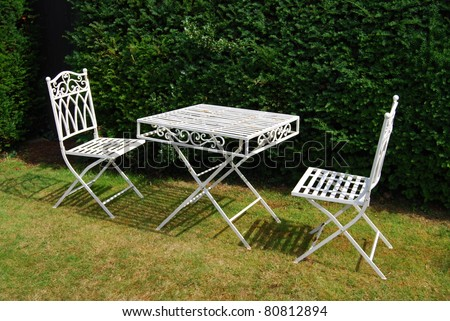 White metal garden furniture on a grass lawn - table and two chairs