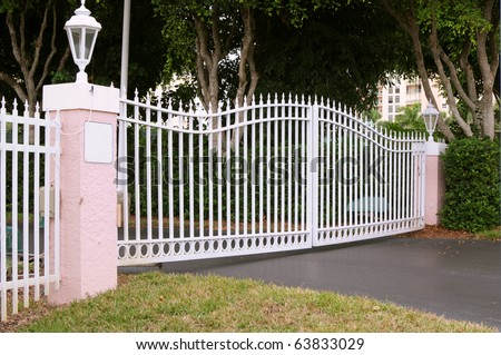White metal gate with pink pillars - stock photo