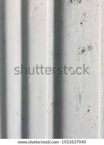 White metal surface with stiffening ribs. White painted metal ribbed surface. There are straight vertical lines of stiffeners on the surface. Foto stock ©