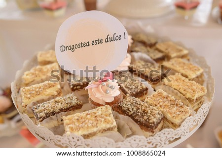 White metal tray with square cakes and one cupcake with the message in Romanian 'Dragostea e dulce' which translates as 'Love is sweet', typical candy bar for weddings or Valentine Day celebration Imagine de stoc ©