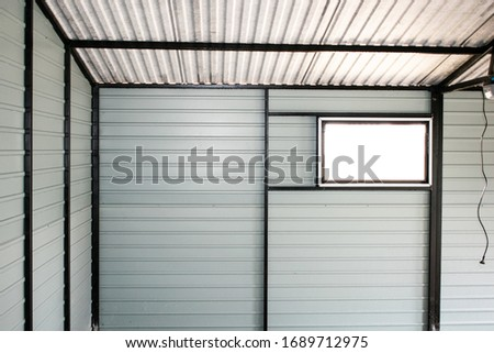 White metall walls and black steel channel. Small window installed. Electric wire hanging from ceiling