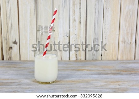 white milk in glass milk bottle with red and white striped straw on whitewashed wood