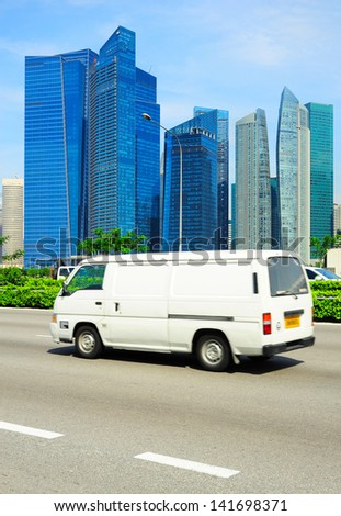 White minibus on the road in Singapore. Blured motion