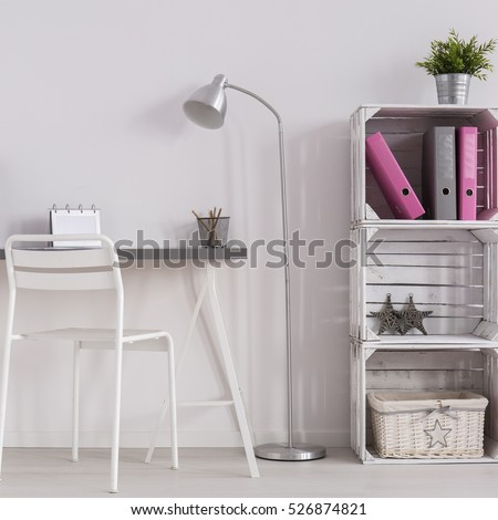 White minimalist home office with simple desk, standing lamp, white chair and DIY bookcase