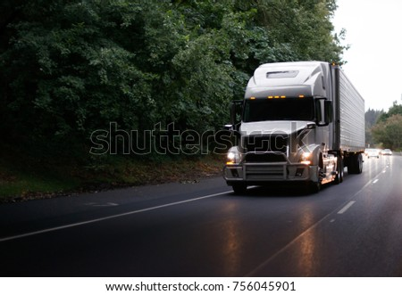 White modern big rig semi truck with grille guard and turn on headlights and reefer semi trailer running on evening road with green trees and light reflection on the road surface