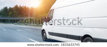 White modern delivery small shipment cargo courier van moving fast on motorway road to city urban suburb. Busines distribution and logistics express service. Mini bus driving on highway day. banner Foto stock ©