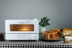 white modern design toaster oven is on the table with homemade sweet potato butter toast breads on grey cement wall background in the kitchen room for breakfast