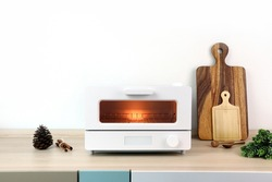white modern design toaster oven is on the wooden table with white cement wall background in minimal design kitchen for making breakfast sliced toasts breads