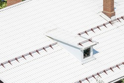 White modern flat roof from texture corrugated metal with dormer window and smokestack