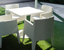 White modern garden dining table and four chairs on green yard. White clean plastic resin outdoor furniture.