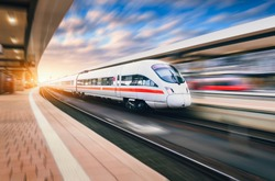 White modern high speed train in motion on railway station at sunset. Train on railroad track with motion blur effect in Europe in evening. Railway platform. Industrial landscape. Railway tourism