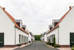 White modern houses with an orange roof in Thorn, Limburg, The Netherlands, a village known for its white houses and buildings. Symmetrical street with green details, greenery and plants