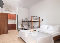 White modern interior of family suit bedroom with classic double bed, bunk bed with metal stairs, wooden kitchen cabinets in single space of small room hotel studio apartment