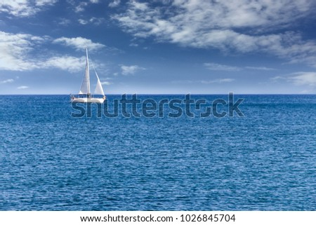 White modern yacht sailboat sailing alone on calm blue sea waters on a beautiful sunny day with blue sky and white clouds.  #1026845704