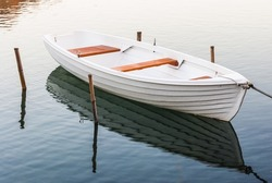 White moored boat on a river with reflection