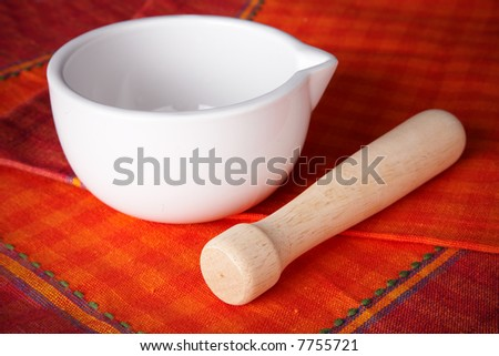 White mortar over a red and orange tablecloth