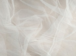 White mosquito net fabric texture with folds. Wavy chiffon background. Full frame of crumpled white cloth material texture. Abstract white net fabric pattern for patterns and designs.