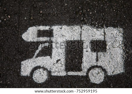 white motor home is painted on the asphalt on a parking spot for caravans