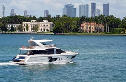 White motor yacht cruising by luxury homes on Star Island in Miami Beach,Florida with downtown Miami tall building skyline in the far background.