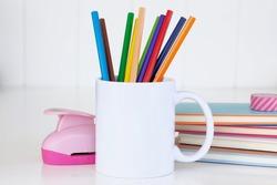 White mug mockup. Blank mug. Coffee mug mockup with colored pencils ,staple and notebooks. 11 oz