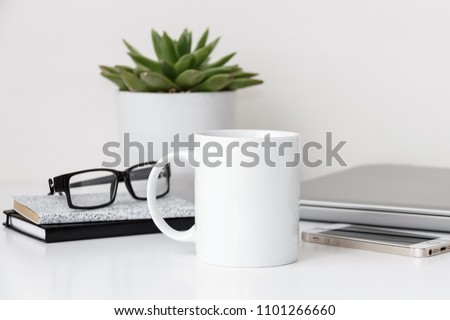White mug mockup, modern workspace with laptop, notebooks, eyeglasses and succulent plant