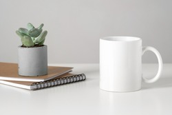 White mug mockup on table in minimalist interior, business concept, succulent and notepads. Template, layout for your design, advertising, logo with copy space. Cup on light gray background.