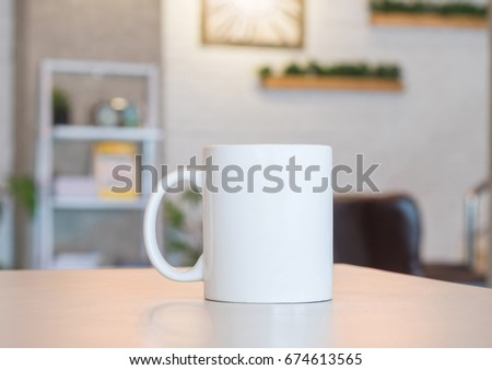 White mug on table and modern room background. Blank drink cup for your design. Can put text, image, and logo. #674613565