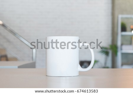 Shutterstock White mug on table and modern room background. Blank drink cup for your design. Can put text, image, and logo.