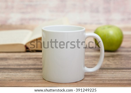 White mug with book and apple behind it
