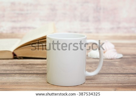 White mug with book behind it