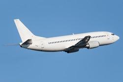 White narrow body Boeing climbing into the sky
