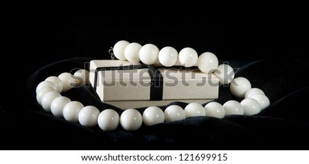 white necklace and gift box on black velvet