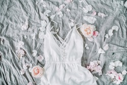 White negligee, pale pastel rose flower buds and petals on grey blanket. Flat lay, top view wedding fashion composition.