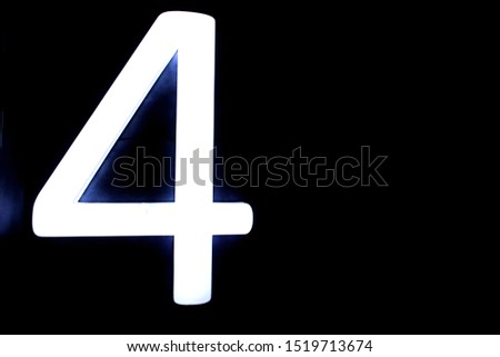White neon digit 4 on black background. figures obtained from fluorescent lamps