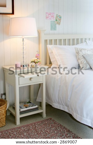 White night table with lamp and magazines