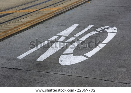 white NO sign painted on concrete street pavement next to cable car tracks